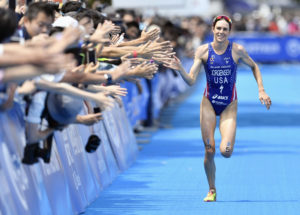 Gwen Jorgensen of the United States gives a high-five to spectators, to winning the world series triathlon in Yokohama for a consecutive fourth time on Saturday, May 14, 2016. (Yohei Fukai/Kyodo News via AP) JAPAN OUT, CREDIT MANDATORY