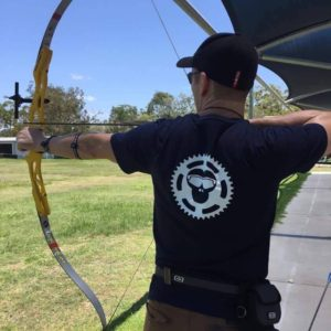Jason practicing his archery with Tri Monkey T Shirt
